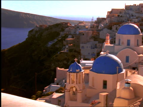 high angle churches with blue domes on cliffside overlooking sea / oia, santorini, greece - イア点の映像素材/bロール