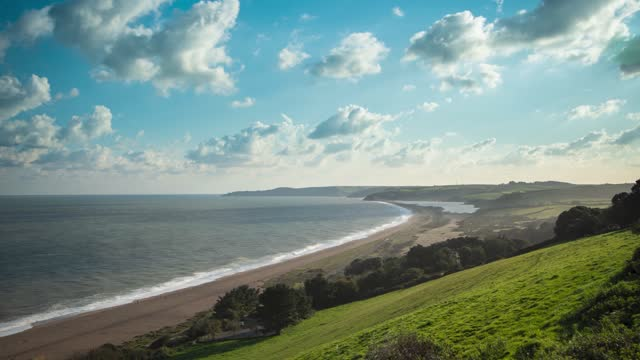 high angle cinematic time lapse of clouds passing shadows over beach as waves hit the shore in slapton, south devon, uk. - beauty in nature stock videos & royalty-free footage