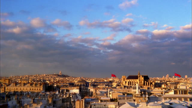 High angle city rooftops and dark clouds w/Sacre Coeur in background / Paris, France