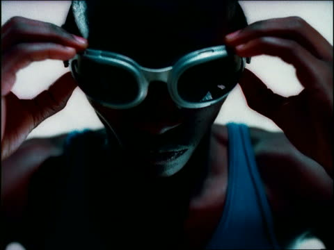 vídeos de stock e filmes b-roll de overexposed high angle close up black male athlete putting on goggles outdoors / namibia, africa - super exposto