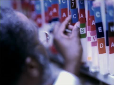 vídeos de stock, filmes e b-roll de high angle close up black male doctor leafing through files on shelf and turning face to camera - quadro médico