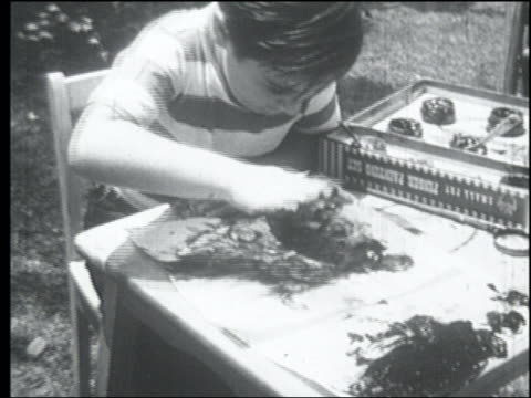 B/W 1952 high angle close up boy making big mess finger painting outdoors