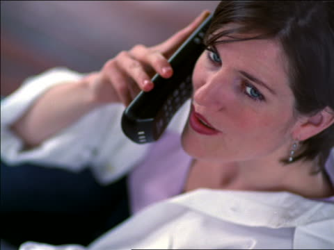 stockvideo's en b-roll-footage met high angle close up face of woman talking on cordless telephone + smiling - draadloze telefoon