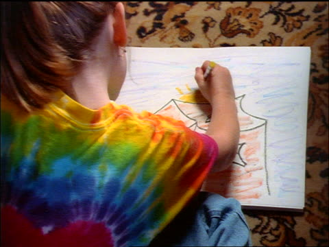 high angle close up girl wearing tie-dye t-shirt sitting on rug doing drawing of house - crayon stock videos and b-roll footage