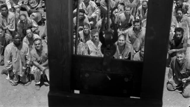 1940 high angle close up guillotine blade falling / wide shot prisoners watching in background / looking away