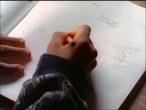 high angle close up hands of Black child doing math homework with pencil