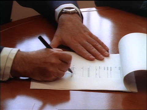 high angle close up hands of men signing contract at desk