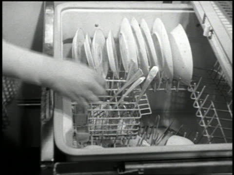 b/w 1959 high angle close up hands of woman putting dishes + soap into dishwasher + then closing dishwasher - lavastoviglie video stock e b–roll