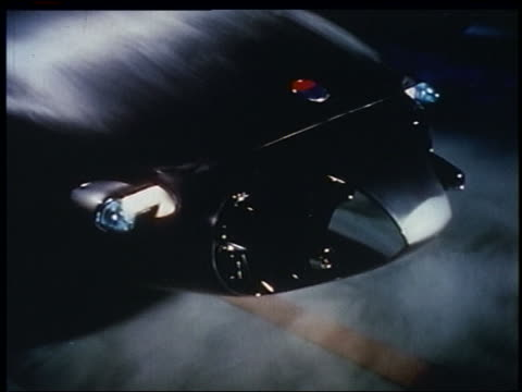 vidéos et rushes de 1956 high angle close up headlights sliding out of black futuristic car hood / smoke on ground - 1956