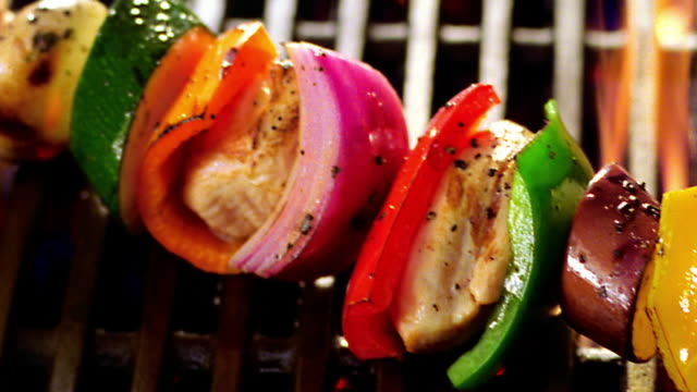 high angle close up pan kebab with chicken + vegetables cooking on flaming grill - peperone video stock e b–roll