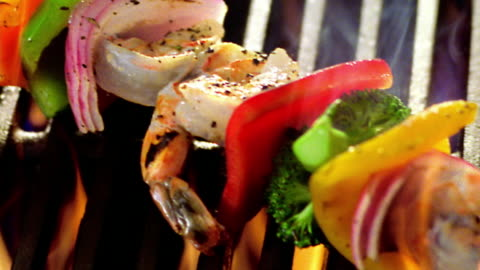 vídeos y material grabado en eventos de stock de high angle close up pan kebab with shrimp + vegetables cooking on flaming grill - cocido a la parrilla
