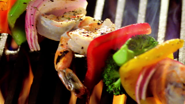 high angle close up PAN kebab with shrimp + vegetables cooking on flaming grill