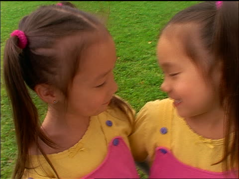 vídeos y material grabado en eventos de stock de high angle close up korean twin girls looking at each other + laughing outdoors - coreano oriental