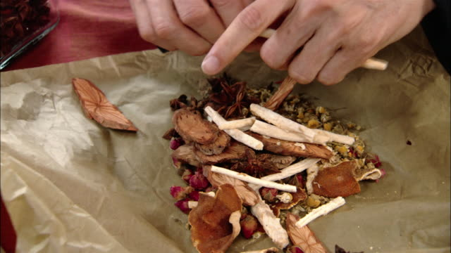 high angle close up man breaking up herbs and wrapping them in a packet - kräuter stock-videos und b-roll-filmmaterial