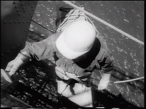 B/W 1964 high angle close up man in hard hat painting newly constructed Verrazano Bridge / NYC
