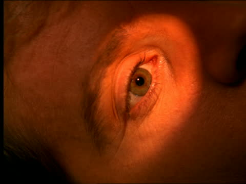 high angle close up man's eye being illuminated by light / looking up, down + around - dejaover点の映像素材/bロール