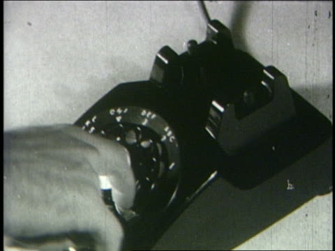 b/w 1950 high angle close up man's hand dialing on rotary phone - rotary phone stock videos and b-roll footage