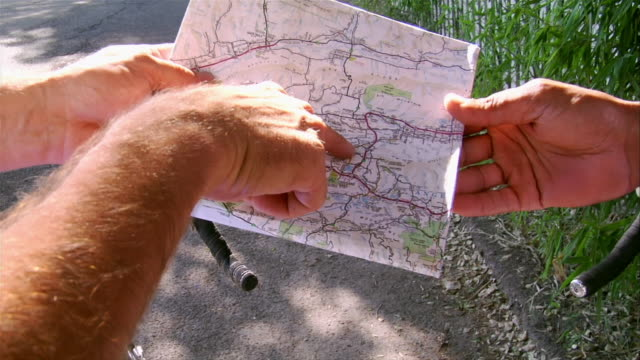 High angle close up men pointing out route on map