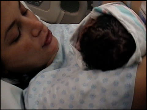 High angle close up mother holding newborn baby in hospital bed