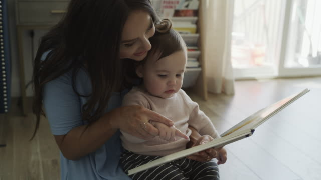 high angle close up of mother and baby daughter sitting on floor reading book / bluffdale, utah, united states - childhood stock videos & royalty-free footage