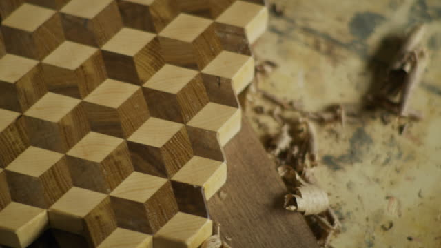 vídeos de stock, filmes e b-roll de high angle close up of wood shavings near wood with cube pattern / provo, utah, united states - provo