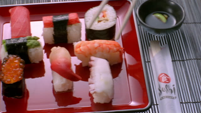 high angle close up pan sushi arranged on glossy red plate / piece of sushi being picked up with chopsticks - vassoio video stock e b–roll