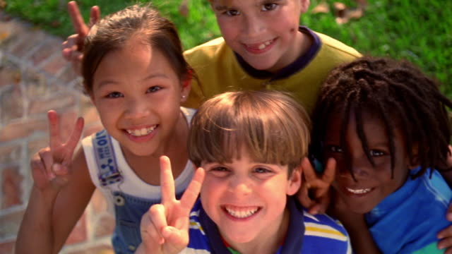high angle close up PAN PORTRAIT Asian girl, Black boy + two blond boys looking up at camera + giving peace sign
