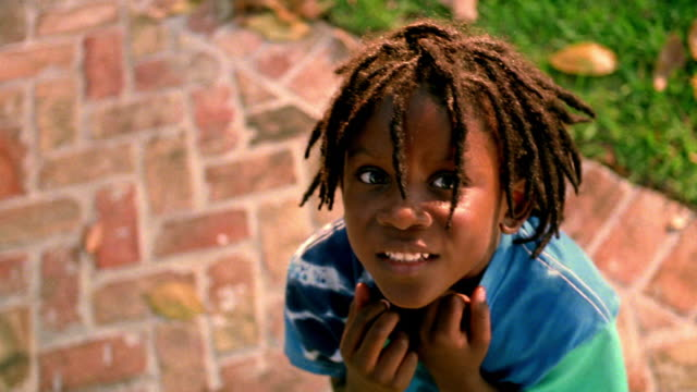 high angle close up pan portrait black boy with dreadlocks looking up at camera + smiling outdoors - locs hairstyle stock videos & royalty-free footage