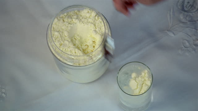 High angle close up powdered milk being scooped out of canister and mixed with water
