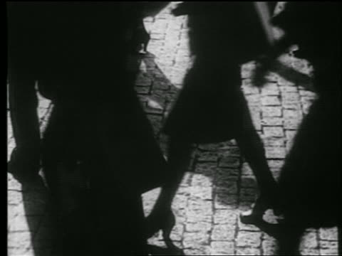 b/w 1939 high angle close up shadows + feet of crowd walking on cobblestone street / nyc / documentary - cobblestone stock videos & royalty-free footage
