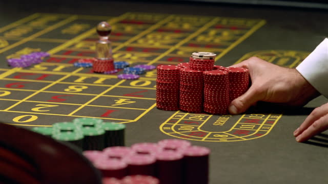 High angle close up sliding chips across roulette table