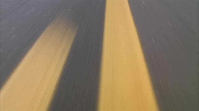 high angle close up speeding over yellow lines on road - zweispurige strecke stock-videos und b-roll-filmmaterial
