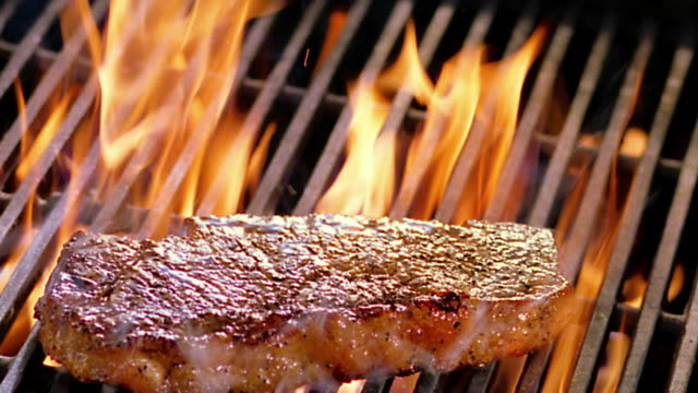 high angle close up steak being flipped over by spatula on flaming grill - 肉点の映像素材/bロール