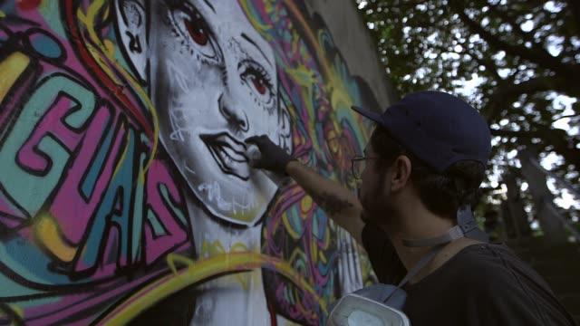vídeos de stock, filmes e b-roll de high angle close up, three graffiti artist spray paint colourful graffiti on a wall in rio de janeiro on june 7th, 2013. no sound - high street