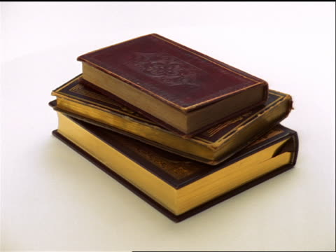 high angle close up three old leather bound books rotating on white background