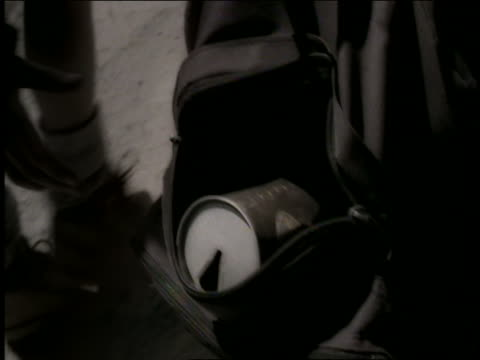 high angle close up tracking shot hand of boy placing can in backpack of other boy walking on path