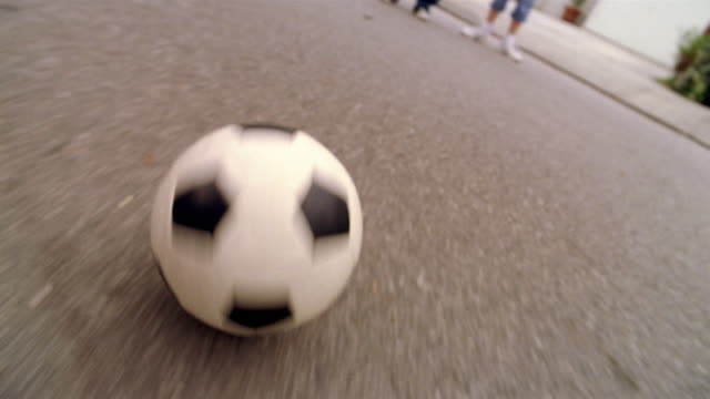 High angle close up tracking shot soccer ball rolling across street / being stopped and kicked by child's foot