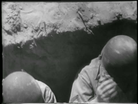 vidéos et rushes de b/w 1952 high angle close up two soldiers in foxhole in desert before hbomb explosion / yucca flats nevada - 1952