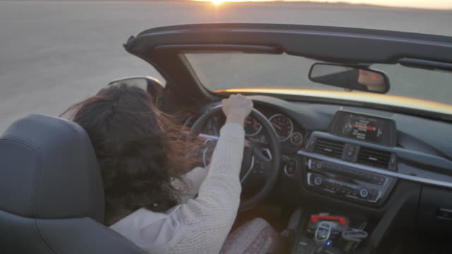 high angle close up, woman drives convertible in desert at sunset - convertible stock videos & royalty-free footage