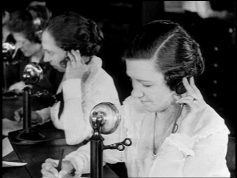 vidéos et rushes de b/w 1919 high angle close up women at table answering telephones + writing / newsreel - 1910 1919