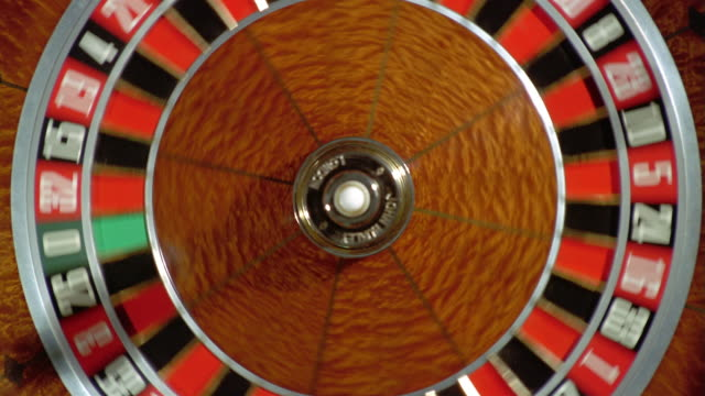 high angle close up zoom out overhead view of a roulette wheel spinning - roulette stock videos and b-roll footage