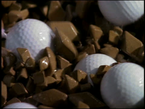 High angle close up zoom out to medium shot golf balls on conveyor belt in factory