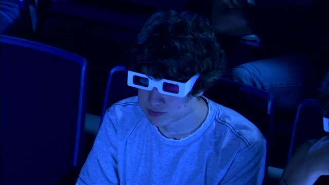vídeos de stock, filmes e b-roll de high angle close-up of a boy eating popcorn with both hands as he watches a 3d movie. - óculos de terceira dimensão