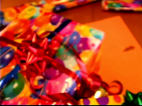 high angle close-up of a pile of colorfully wrapped presents pushing into an extreme close-up of the red bow. - bald head island stock videos & royalty-free footage