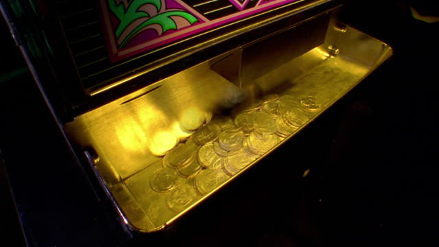 high angle ms coins pouring out of slot machine in to golden tray - casino stock-videos und b-roll-filmmaterial