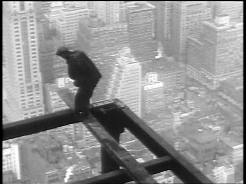 vidéos et rushes de b/w 1930 high angle construction worker sitting down on plank on top of empire state building / nyc - empire state building