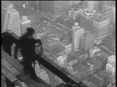 vidéos et rushes de high angle construction worker smoking cigarette + walking on girder of empire state building - empire state building