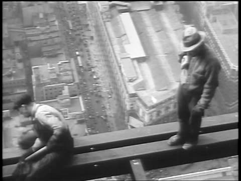 vidéos et rushes de b/w 1930 high angle pan construction workers on girder of empire state building under construction - empire state building