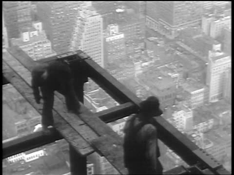 high angle construction workers walking on + moving planks on top of empire state building / nyc - empire state building stock videos & royalty-free footage