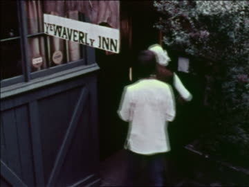 """1969 high angle couple entering """"ye waverly inn"""" restaurant / greenwich village, nyc / industrial - greenwich village stock videos & royalty-free footage"""